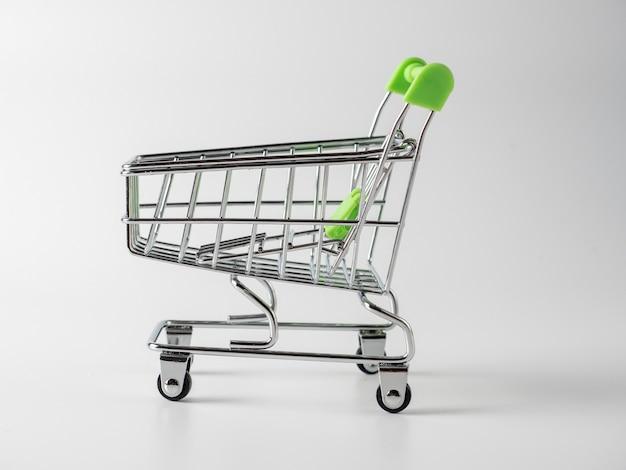 Close-up di carrelli della spesa verde su sfondo bianco. concetto di vendita. carrello, prodotti. vista laterale