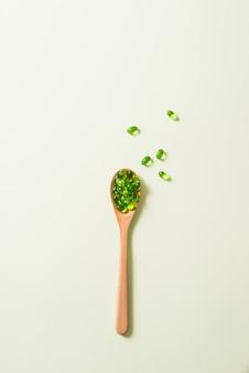 Close up verde capsule softgel con cucchiaio di legno isolato su sfondo bianco.