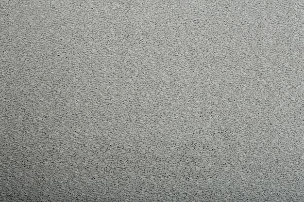 Primo piano sulla carta da parati grigia di struttura del tappeto