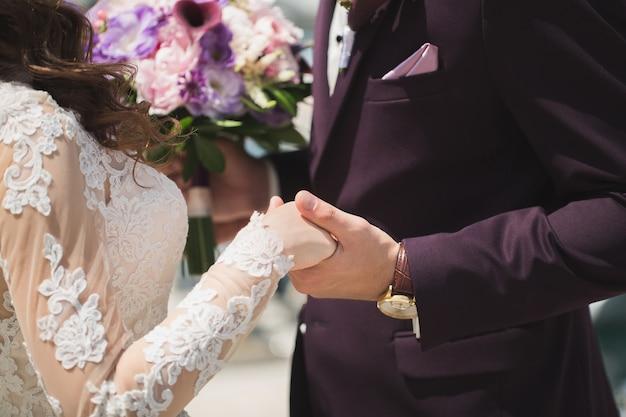 Primo piano della sposa della holding della mano dello sposo