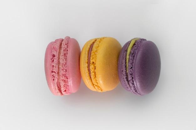 Gruppo ravvicinato di 3 pile di macarons colorati su sfondo bianco, colore pastello, viola, rosa e giallo, mirtillo, fragola e macaron arancione
