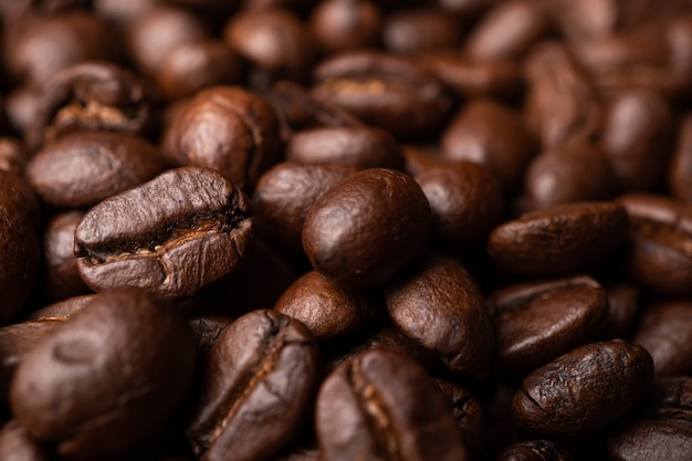 Chiuda su dei chicchi di caffè neri del gruppo. caffè espresso nero forte, fondo di fondi di caffè, consistenza
