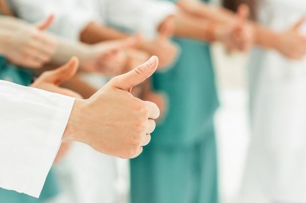 Primo piano gruppo di medici che mostrano i pollici in su