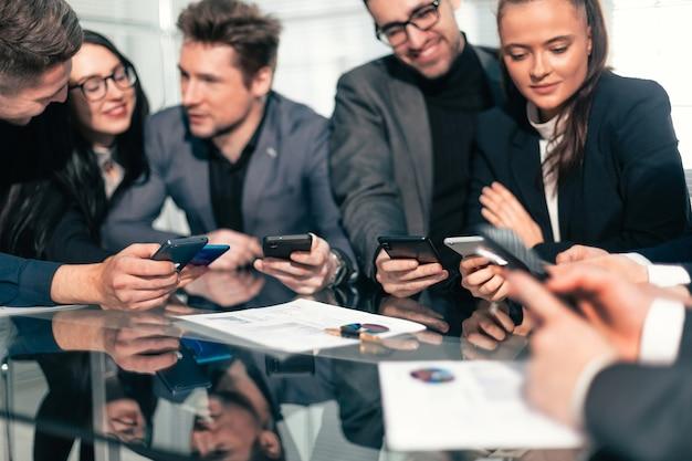 Avvicinamento . gruppo di dipendenti che utilizzano i propri smartphone sul posto di lavoro