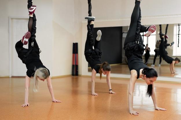 Close-up gruppo di ragazze che appendono su elastici elastici in palestra.