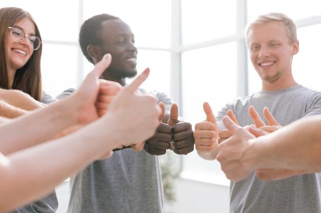Avvicinamento. gruppo di persone con idee simili che mostrano i pollici in su. concetto di successo