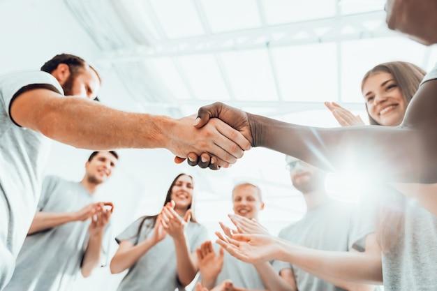 Avvicinamento. un gruppo di studenti applaude due avversari durante un briefing aziendale. affari e istruzione
