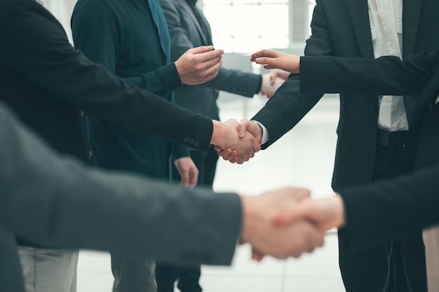Avvicinamento. un gruppo di giovani imprenditori che si stringono la mano. concetto di mutua assistenza
