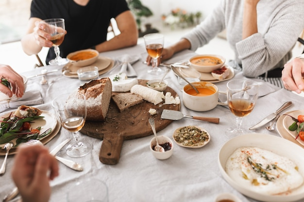 Primo piano un gruppo di giovani seduti al tavolo pieno di cibo delizioso pranzando insieme