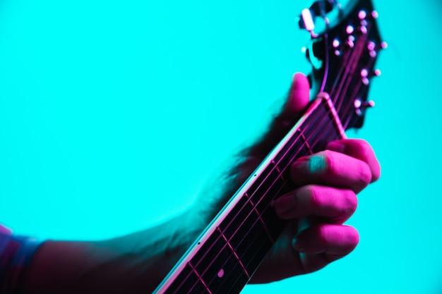 Primo piano della mano del chitarrista che suona la chitarra, macro. concetto di pubblicità, hobby, musica, festival, intrattenimento. persona che improvvisa ispirata. copyspace per inserire immagine o testo. illuminato al neon colorato.