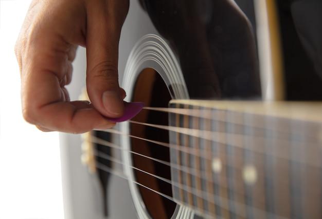 Primo piano della mano del chitarrista che suona la chitarra, ripresa macro. concetto di pubblicità, hobby, musica, festival, intrattenimento. persona che improvvisa ispirata. copyspace per inserire immagine o testo.