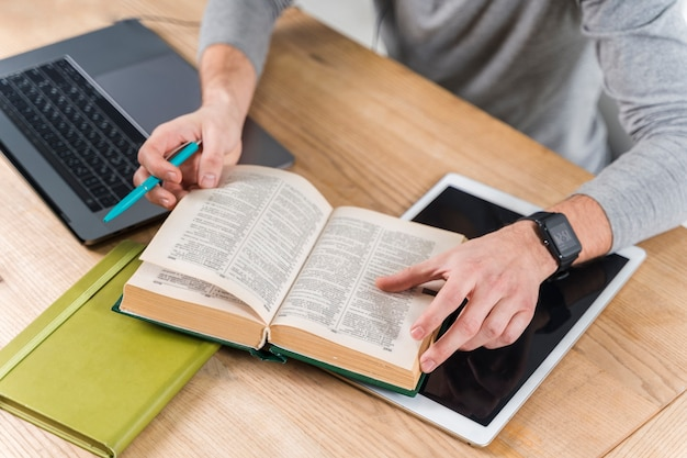 Ragazzo del primo piano che studia con il dizionario