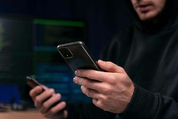 Primo piano hacker che tiene smartphone