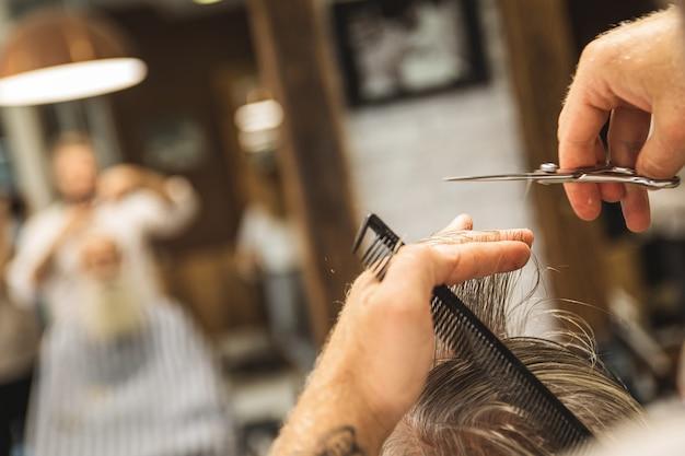 Primo piano del parrucchiere hannds con le forbici che fa taglio di capelli alla moda