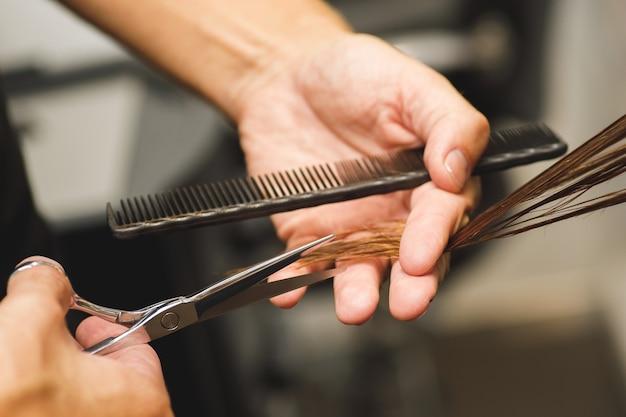 Primo piano delle mani maschile del parrucchiere durante il taglio dei capelli femminili