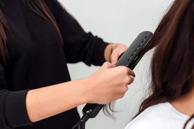 Primo piano di un parrucchiere che raddrizza capelli marroni lunghi con i ferri di capelli.