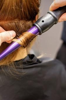 Primo piano delle mani dei parrucchieri utilizzando un ferro arricciacapelli per i riccioli di capelli in un salone di bellezza