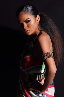 Primo piano metà corpo di 20s donna asiatica con moda trucco stile tribù collina africana. ragazza con la pelle abbronzata capelli alfro esprimere una sensazione forte, sorridere con accessori etnici colorati su sfondo nero