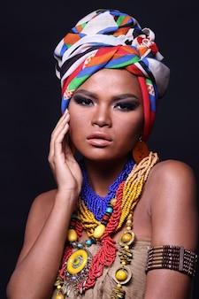 Primo piano metà corpo di 20s donna asiatica con moda trucco stile tribù collina africana. la ragazza con la pelle abbronzata esprime una sensazione forte, sorridente, felice con accessori etnici colorati su sfondo nero