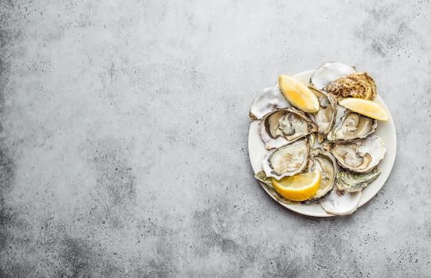 Close-up di mezza dozzina di fresche ostriche aperte e gusci con spicchi di limone su una piastra, vista dall'alto, grigio cemento rustico sfondo