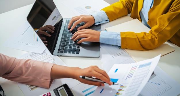 Primo piano contabile della mano che tiene la penna puntata sul grafico dei documenti per la riunione del team nella stanza dell'ufficio. concetto di finanza e contabilità