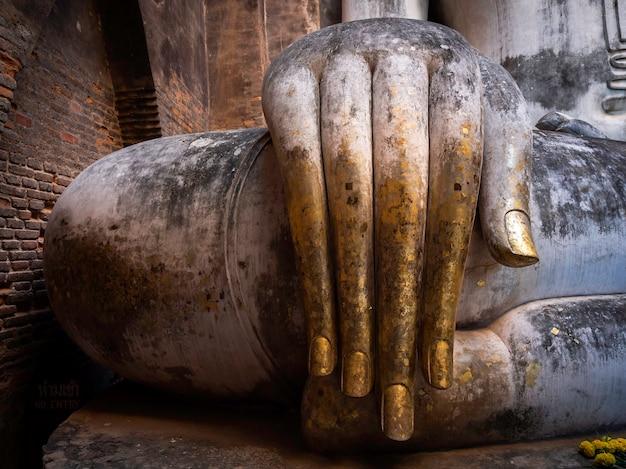 Primo piano della mano dell'antica statua del buddha all'interno della chiesa del tempio wat sri chum, il famoso punto di riferimento nel parco storico di sukhothai, patrimonio mondiale dell'unesco in thailandia.