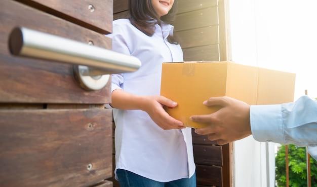 La fine sulla mano della donna dell'asia è riceve una scatola dal fattorino con la luce del sole