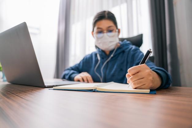 Primo piano della mano di una ragazza adolescente asiatica che indossa le cuffie imparando la lingua online, usando il laptop, guardando lo schermo, facendo compiti scolastici a casa, scrivendo note, educazione a distanza