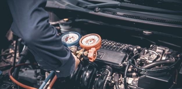 La mano del primo piano del meccanico di automobile sta usando l'indicatore del collettore per riempire i condizionatori d'aria dell'automobile
