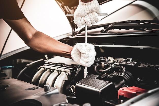 La mano del primo piano del meccanico automatico sta usando la chiave per riparare il motore di un'auto