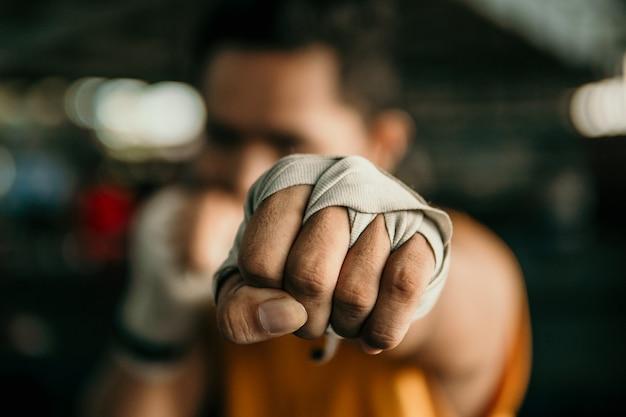 Chiuda in su del pugile della mano nella fasciatura di incarto fare un movimento di jab sul ring