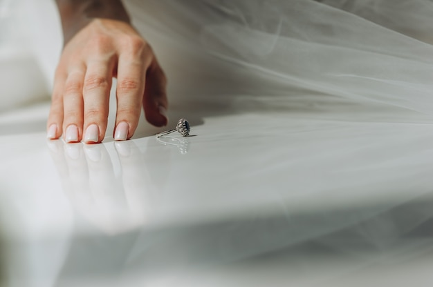 Primo piano della mano della sposa con una bella manicure delicata e un anello vintage con un diamante blu sul davanzale della finestra. mattina della sposa.