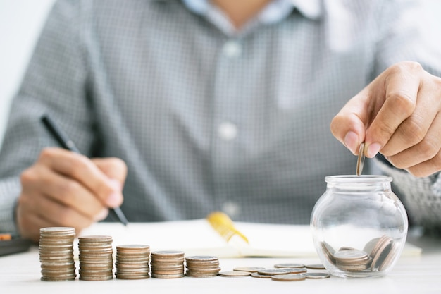 Chiuda sulla calcolatrice di contabilità dell'uomo di affari della mano con le monete dei soldi di risparmio impilate la riga con la mano che mette le monete in vetro della brocca
