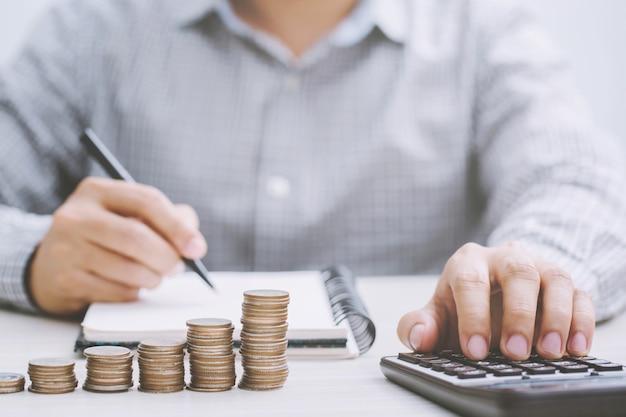 Chiuda sulla contabilità dell'uomo di affari della mano con le monete dei soldi di risparmio impilate fila con la mano che mette le monete in vetro della brocca