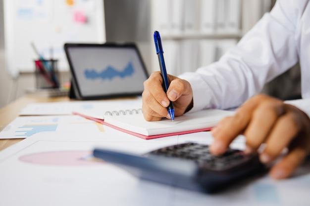 Primo piano della mano dell'uomo d'affari che preme sulla calcolatrice per controllare il reddito finanziario e il profitto