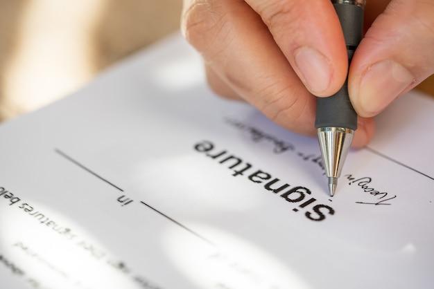 Mano ravvicinata di una donna d'affari che tiene una penna per firmare il documento del contratto