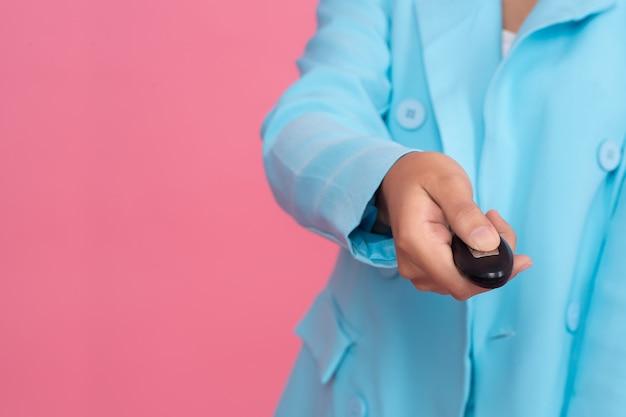 Chiuda sulla mano della donna di affari che tiene chiave astuta sul rosa