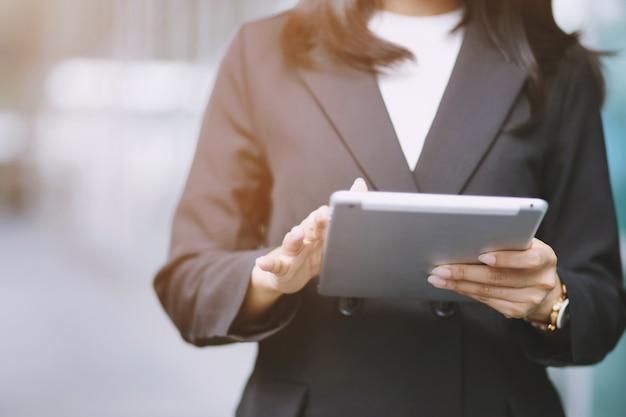 Chiuda sulla donna di affari della mano che lavora usando un dispositivo pc della compressa digitale mentre levandosi in piedi davanti alle finestre in un edificio per uffici che trascura la città.