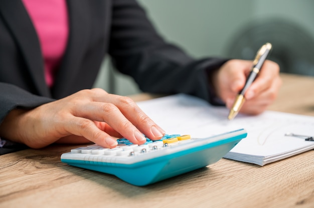 Mano ravvicinata di imprenditrice che utilizza la macchina per il calcolo delle finanze domestiche o delle tasse sulla macchina, concetti finanziari e contabili,