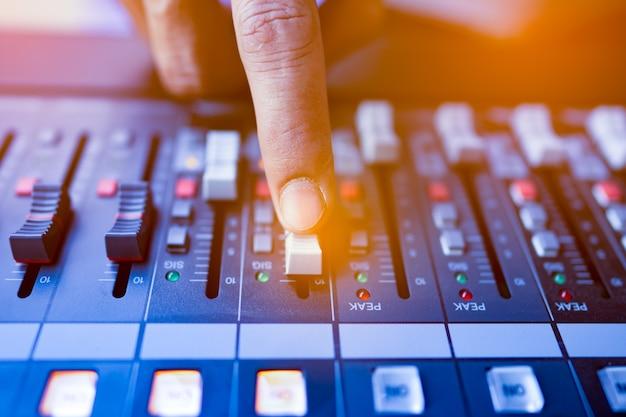 Chiudere la mano sul fondo della console di mixaggio della musica