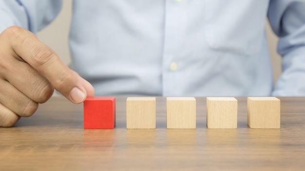 La mano del primo piano sceglie i blocchi di legno del giocattolo del cubo impilati senza grafica per il concetto di progetto di affari.