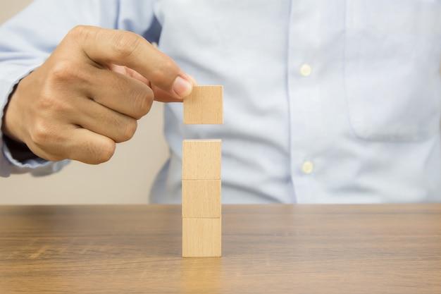 La mano del primo piano sceglie i blocchi di legno del giocattolo del cubo impilati senza grafica.