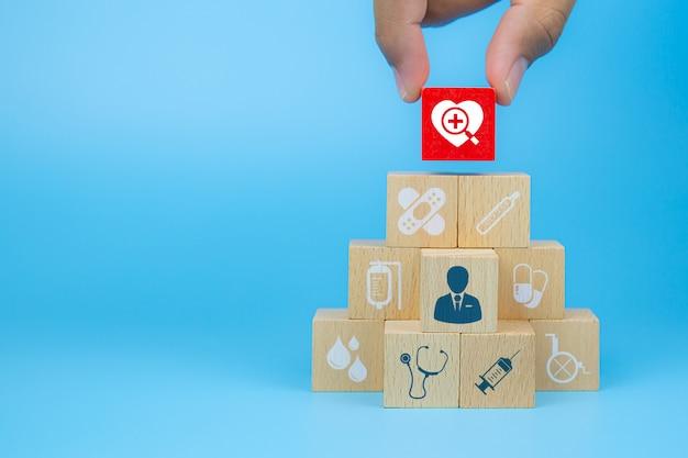 La mano del primo piano sceglie i blocchi di legno di un giocattolo del cubo con un'icona del cuore impilata in una forma della piramide per i concetti medici e dell'assicurazione malattia.