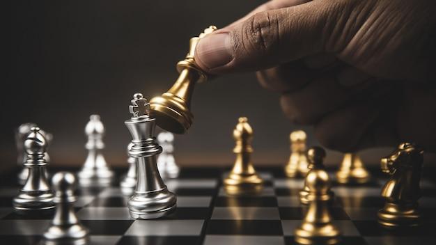 Primo piano mano scegliere gli scacchi d'oro per combattere con gli scacchi d'argento.