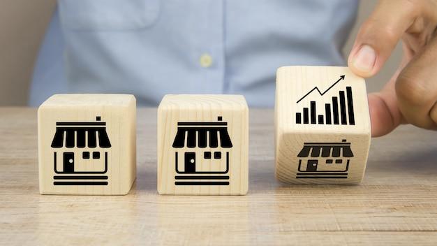 La mano del primo piano sceglie l'icona del grafico sui blocchi di legno del giocattolo del cubo posizionati in linea con l'icona del negozio di affari di franchising.