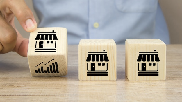 La mano del primo piano sceglie l'icona del grafico sui blocchi di legno del giocattolo del cubo posizionano in linea con l'icona del negozio di affari di franchising.