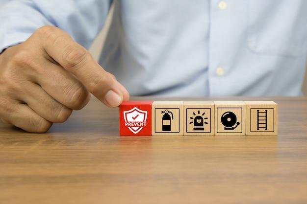 La mano del primo piano sceglie l'icona di prevenzione sui blocchi di legno del giocattolo del cubo accatastati con l'icona di prevenzione dell'uscita di fuoco.