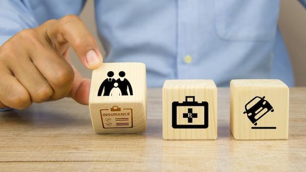 La mano del primo piano sceglie il blocco di legno con l'icona di assicurazione.