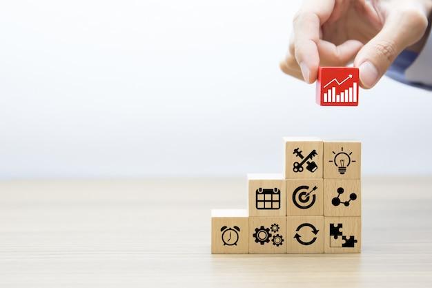 La mano del primo piano sceglie i blocchi di legno impilati con l'icona del grafico su altre icone di affari.
