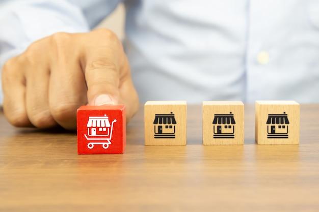 Chiudere la mano sceglie la pila di blocchi di giocattoli in legno cubo con l'icona del negozio di affari in franchising nel carrello